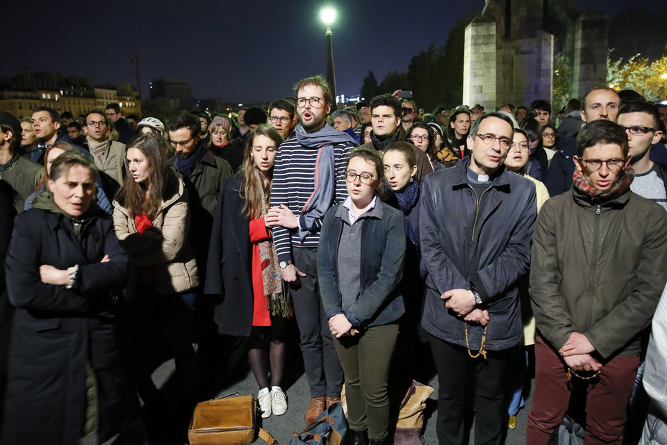 Photo - People pray as Notre Dame cathedral is burning in Paris, Monday, April 15, 2019. A catastrophic fire engulfed the upper reaches of Paris' soaring Notre Dame Cathedral as it was undergoing renovations Monday, threatening one of the greatest architectural treasures of the Western world as tourists and Parisians looked on aghast from the streets below. (AP Photo/Francois Mori)