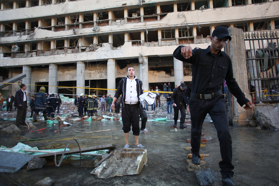 Photo - Egyptian police officers walk thorough water that came out of the underground water pipe after a blast at the Egyptian police headquarters as firefighters check the damage in downtown Cairo, Friday, Jan. 24, 2014. A car bomb struck the Egyptian police headquarters in downtown Cairo on Friday, killing at least several people and wounding dozens, the country's state media reported. (AP Photo/Khalil Hamra)