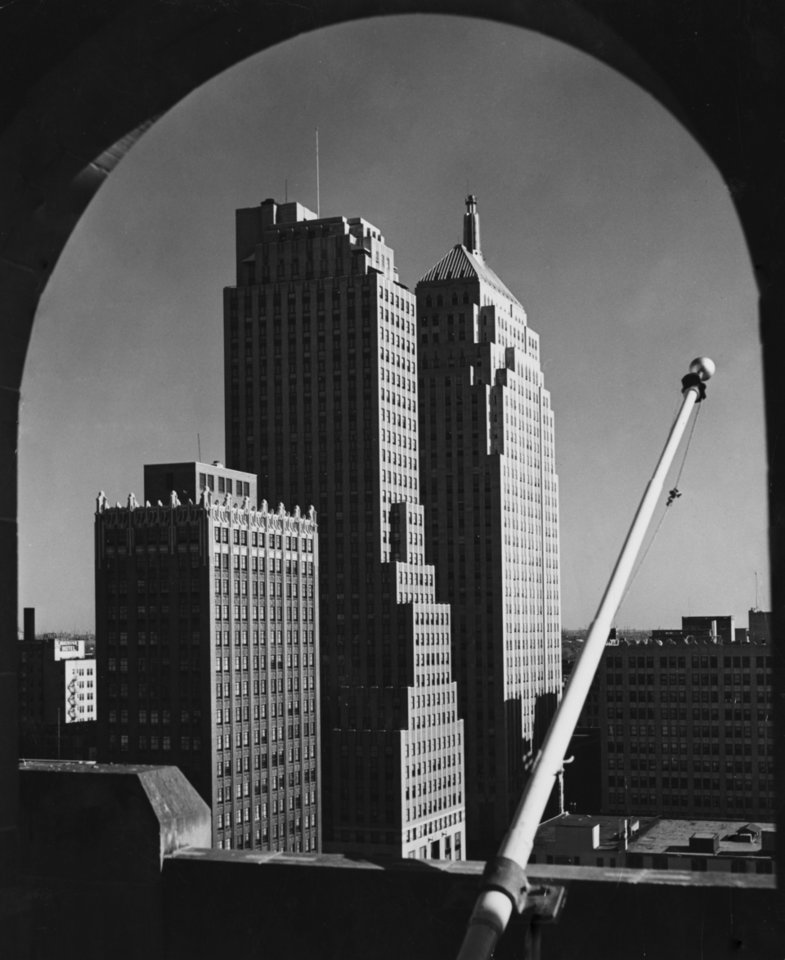 OKLAHOMA CITY / SKY LINE / OKLAHOMA / 1948:  The flagpole on the federal building will be bare this week, while the building engineer tries to slant it so the flag will fly full in the breeze.  Fred Shaw, postmaster, said drafts from the building's airshafts has been wrapping the flag around the pole.  When the flag flies again at the end of the week, Shaw said, the pole will have been reset at the new, even angle.  Staff photo by Richard B. Meek.  Photo dated 04/13/1948 and published on 04/14/1948 in the Daily Oklahoman.