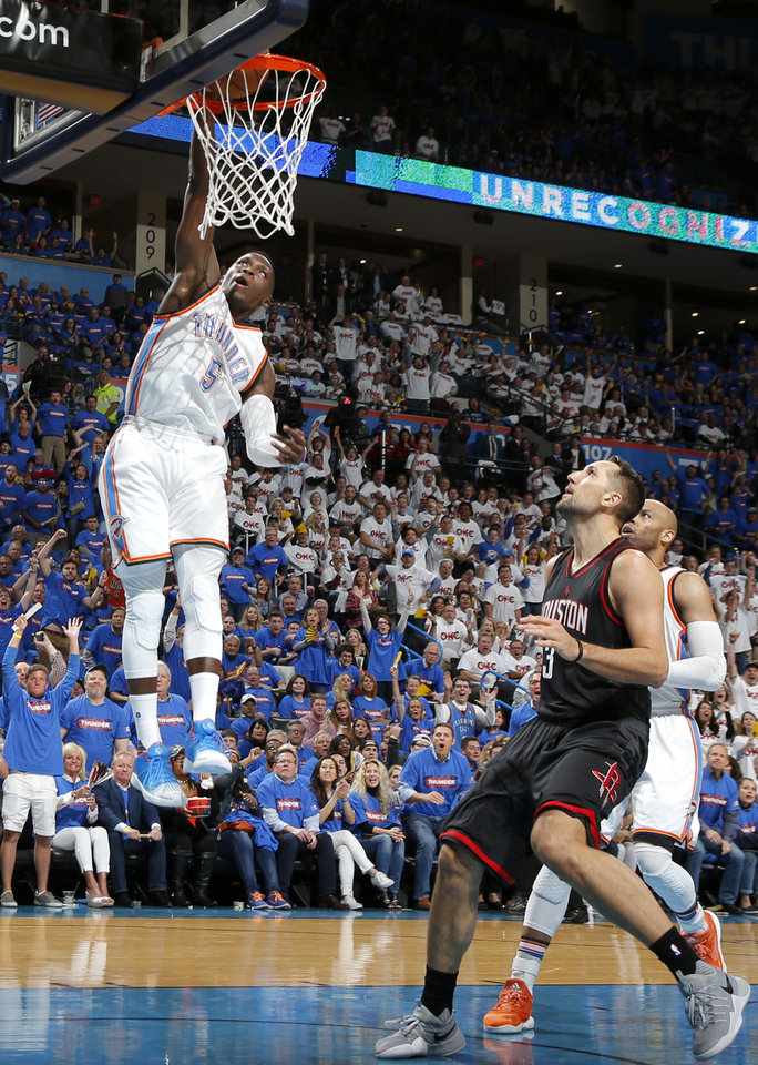 Photo - Oklahoma City's Victor Oladipo (5) dunks in front of Houston's Ryan Anderson (3) during Game 3 in the first round of the NBA basketball playoffs between the Oklahoma City Thunder and the Houston Rockets at Chesapeake Energy Arena in Oklahoma City, Friday, April 21, 2017.  Photo by Nate Billings, The Oklahoman