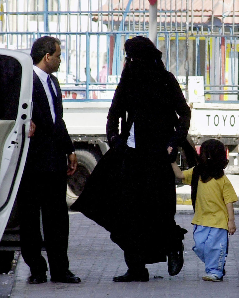 FILE - In this Wednesday, Jan. 25, 2006 picture, Michael Jackson, center, wears an abaya, the traditional Arabic women's veil and all-covering gown, and holds the hand of one of his children, Prince Michael II, also veiled, as they walk toward their car behind a shopping mall in Manama, Bahrain. Jackson, was a reclusive resident of the Gulf island country since being cleared of child molestation charges and was accompanied by his sister, Janet, unseen, and two other children on the shopping outing. A person with knowledge of the situation said Thursday, June 25, 2009 that Jackson has died in Los Angeles at age 50. (AP Photo/Hasan Jamali) ORG XMIT: NYET721