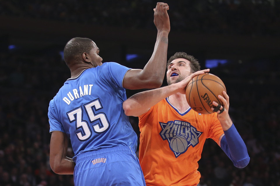 Photo - New York Knicks power forward Andrea Bargnani (77) shoots against Oklahoma City Thunder forward Kevin Durant (35) during the first half of their NBA basketball game at Madison Square Garden, Wednesday, Dec. 25, 2013, in New York. (AP Photo/John Minchillo)