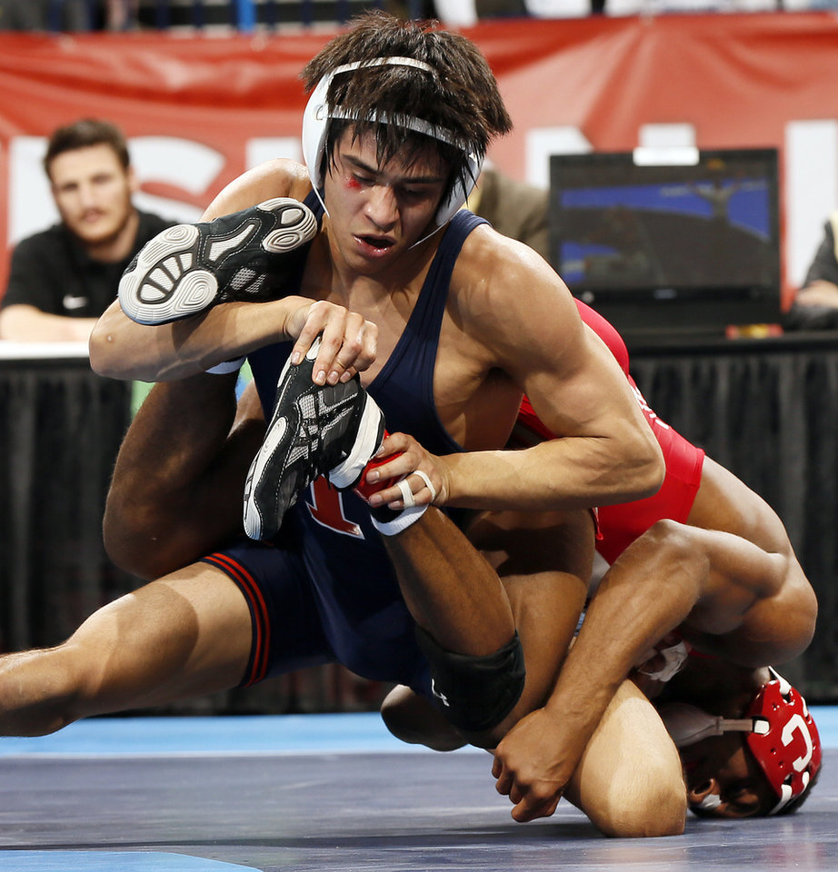 Photo - Illinois' Jesse Delgado wrestles Cornell's Nahshon Garrett for the 125-pound national championship in the 2014 NCAA Div. I Wrestling Championships at Chesapeake Energy Arena in Oklahoma City, Saturday, March 22, 2014. Photo by Nate Billings, The Oklahoman
