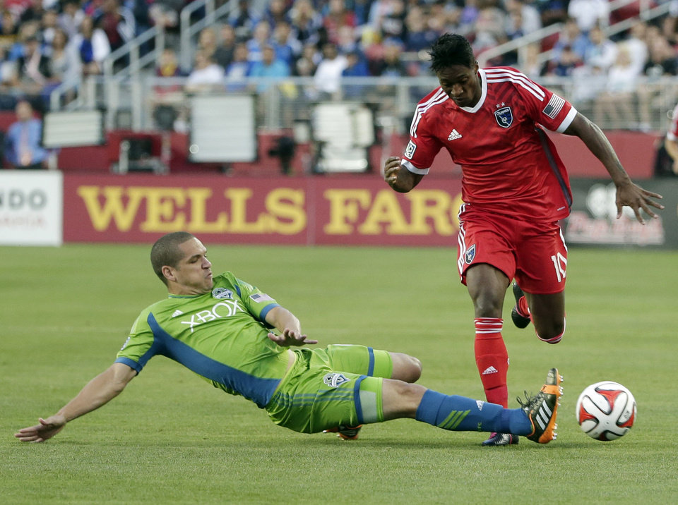 Photo - Seattle Sounders midfielder Osvaldo Alonso, left, makes a slide tackle next to San Jose Earthquakes midfielder Yannick Djalo during the first half of an MLS soccer match Saturday, Aug. 2, 2014, in Santa Clara, Calif. (AP Photo/Marcio Jose Sanchez)