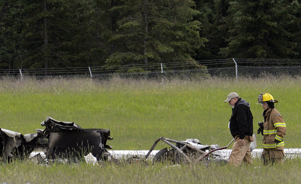 Photo - Investigators look at the remains of a fixed-wing aircraft that was engulfed in flames Sunday July 7, 2013 at the Soldotna Airport in Soldotna, Alaska. Authorities say an air taxi has crashed, killing all 10 people on board. (AP Photo/Peninsula Clarion, Rashah McChesney)
