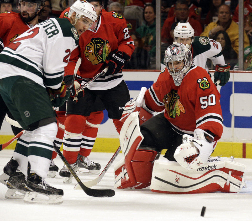 Photo - Chicago Blackhawks goalie Corey Crawford (50), right, blocks a shot by Minnesota Wild's Nino Niederreiter (22) during the first period  in Game 2 of an NHL hockey second-round playoff series in Chicago, Sunday, May 4, 2014. (AP Photo/Nam Y. Huh)