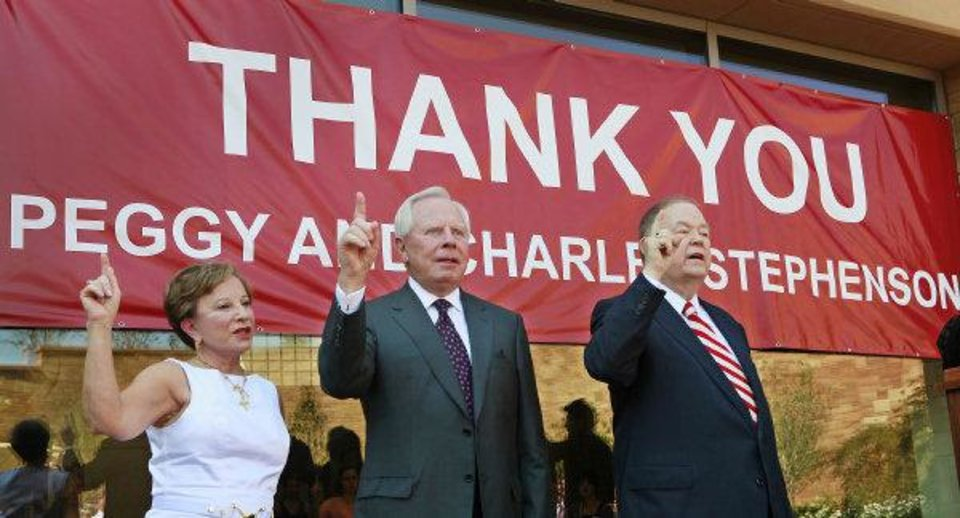 Photo - Peggy and Charles Stephenson and University of Oklahoma President David Boren sing the OU chant Thursday during the dedication of the Peggy and Charles Stephenson Oklahoma Cancer Center. The building is located on the OU Health Sciences Center campus in Oklahoma City. Photo by David McDaniel, The Oklahoman  ORG XMIT: KOD  David McDaniel - The Oklahoman
