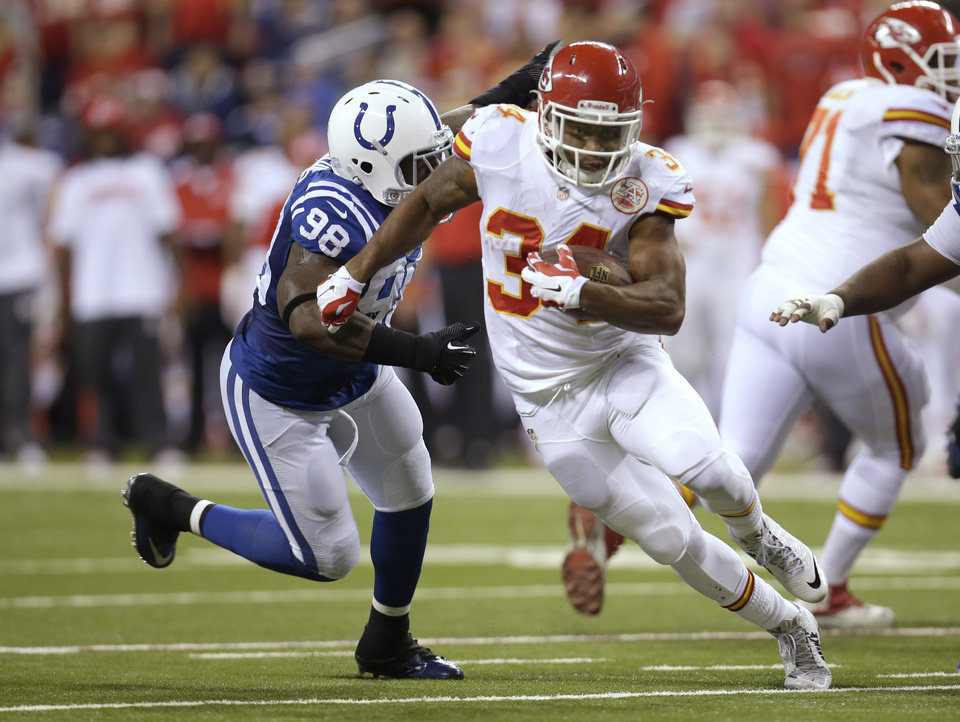 Photo - Kansas City Chiefs running back Knile Davis (34) runs from Indianapolis Colts outside linebacker Robert Mathis (98) during the first half of an NFL wild-card playoff football game Saturday, Jan. 4, 2014, in Indianapolis. (AP Photo/AJ Mast)