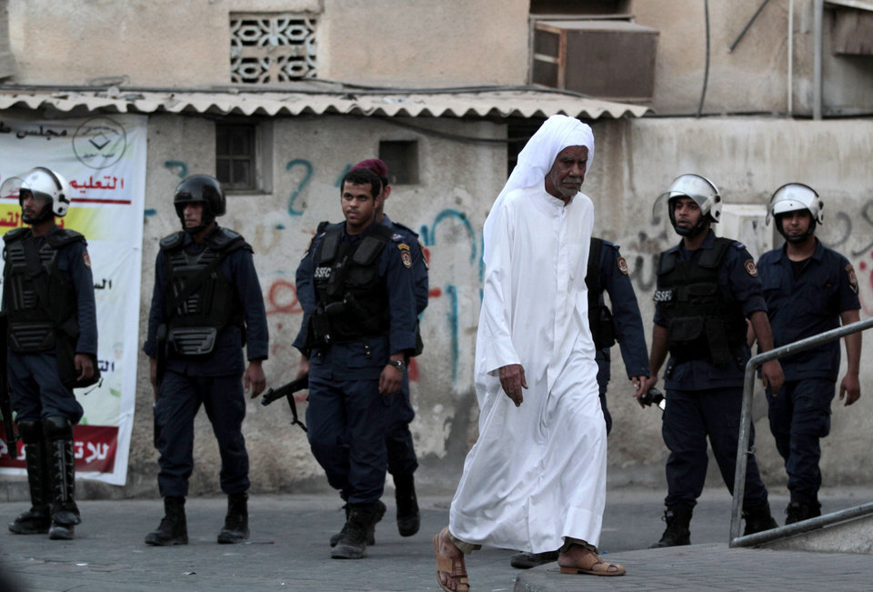 An elderly Bahraini man passes by riot policemen patrolling in Daih, Bahrain, on Saturday, Nov. 3, 2012, where anti-government protesters tried to organize a march despite a ban on protests. A heavy police presence prevented protesters from gathering, and police dispersed and chased small groups through narrow streets as they emerged. (AP Photo/Hasan Jamali)