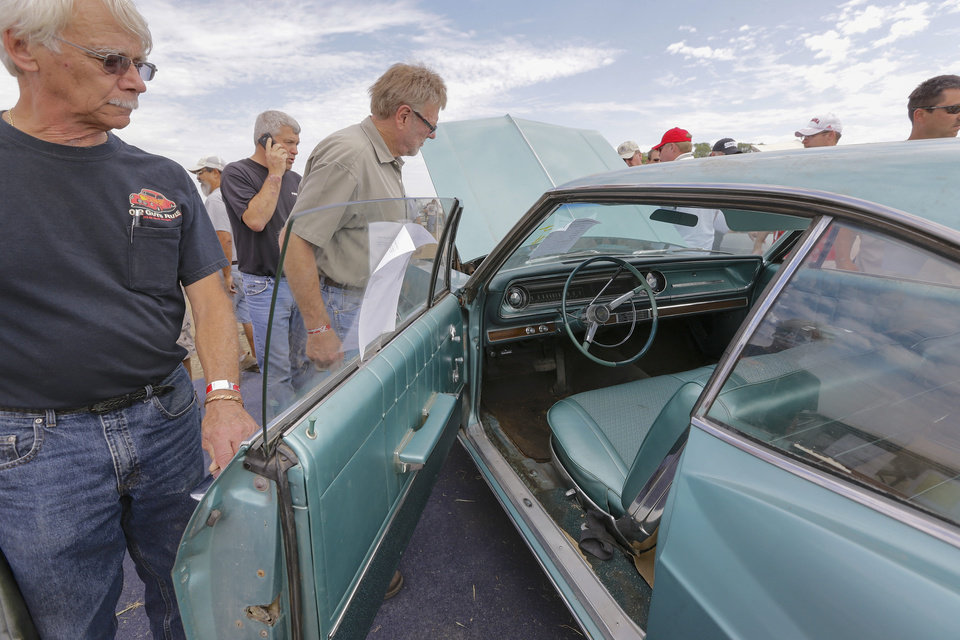 Photo - Car buffs look over 1965 Chevrolet Impala 2 door hardtop during a preview for an auction of vintage cars and trucks from the former Lambrecht Chevrolet dealership in Pierce, Neb., Friday Sept. 27, 2013. The auction takes place on Saturday and Sunday. (AP Photo/Nati Harnik)