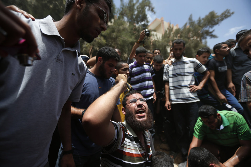 Photo - A Palestinian mourner chants slogans on the grave of a member of the al-Batsh family who were killed in Saturday's Israeli airstrike, during a funeral procession in Gaza City on Sunday, July 13, 2014. The strike hit the home of Gaza police chief Taysir al-Batsh and damaged a nearby mosque as evening prayers ended Saturday, killing at least 18 people, wounding 50 and leaving some people believed to be trapped under the rubble, said Palestinian Health Ministry official Ashraf al-Kidra. (AP Photo/Lefteris Pitarakis)