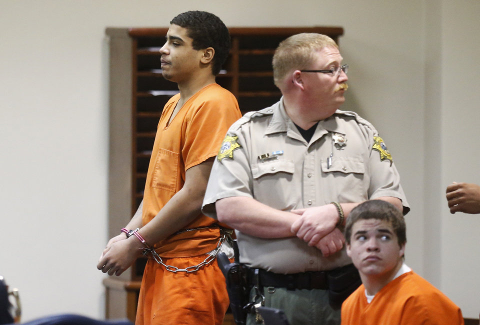 Photo - In this photo shot through a courtroom door Wednesday, defendant Chancey Jones, left, is led from the courtroom after a hearing in Duncan. At right is defendant Michael Jones.  Sue Ogrocki