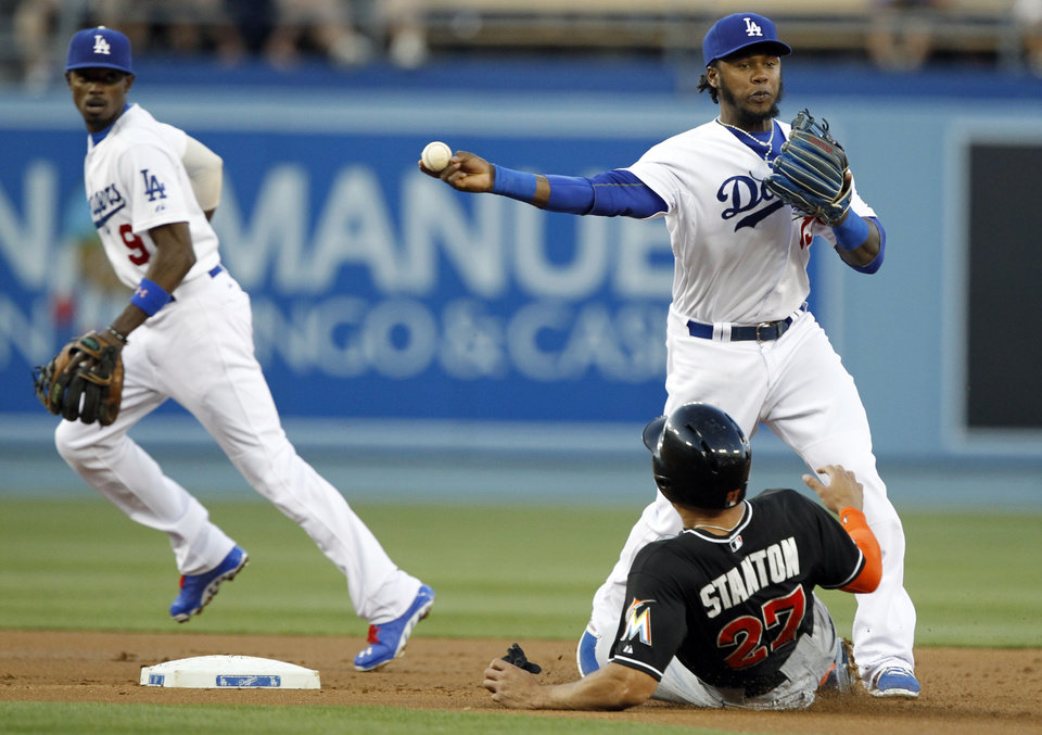 Photo - Los Angeles Dodgers shortstop Hanley Ramirez, top right, turns a double play over Miami Marlins' Giancarlo Stanton (27) with second baseman Dee Gordon (9) watching during the fist inning of a baseball game Wednesday, May 14, 2014, in Los Angeles. Jeff Baker was out at first. (AP Photo/Alex Gallardo)