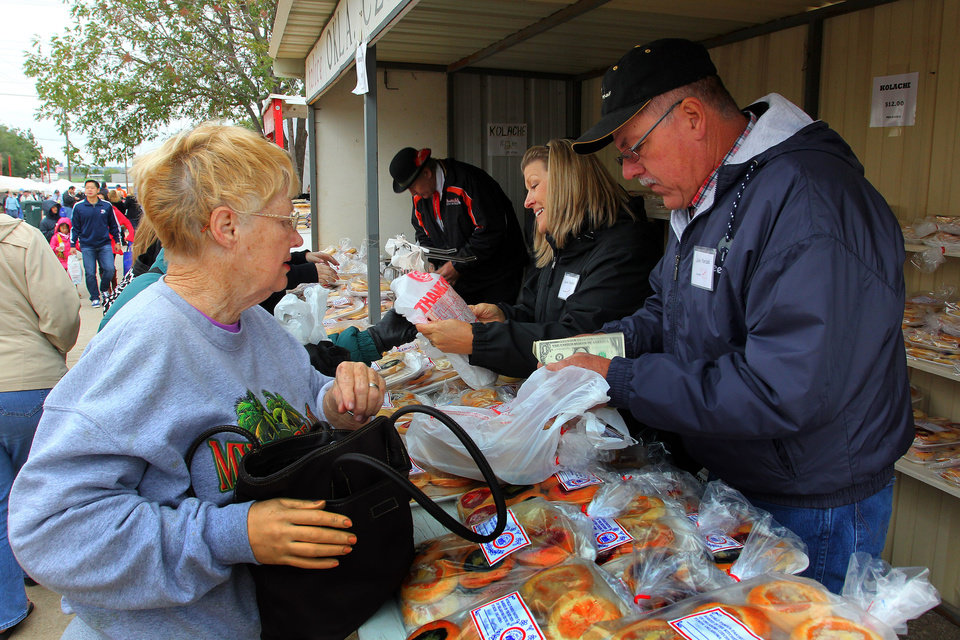 Photo - John Parizek counts change to give to Marge Hester after she purchased kolaces during the 47th annual Czech Festival Saturday in Yukon. PHOTO BY HUGH SCOTT FOR THE OKLAHOMAN