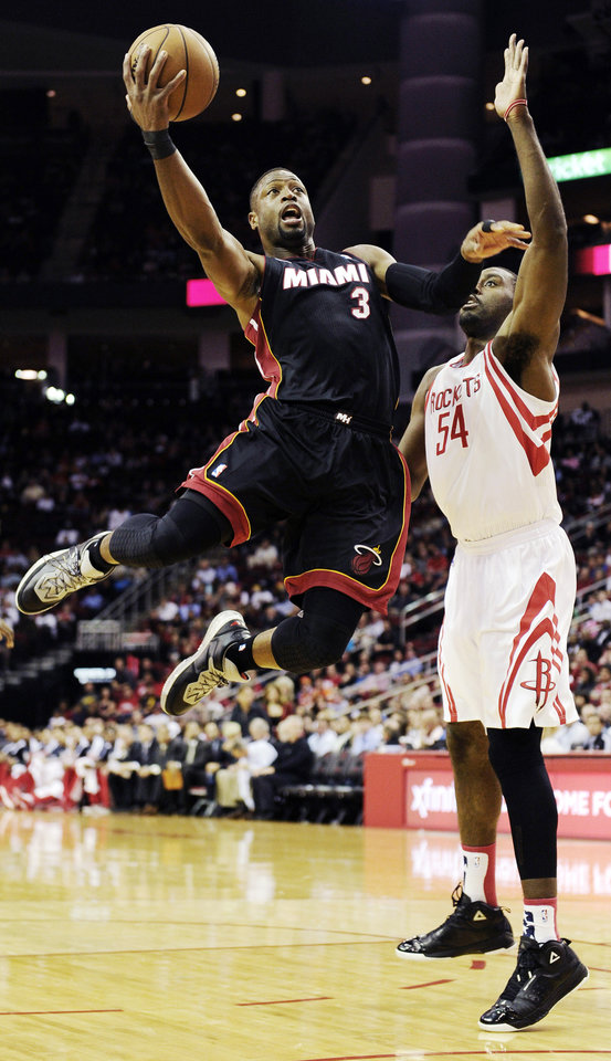 Photo -   Miami Heat's Dwyane Wade (3) goes to the basket in front of Houston Rockets' Patrick Patterson (54) in the first half of an NBA basketball game, Monday, Nov. 12, 2012, in Houston. (AP Photo/Pat Sullivan)