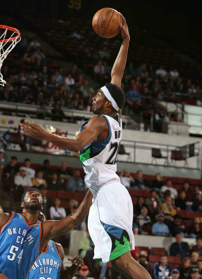 Photo - OKLAHOMA CITY THUNDER NBA BASKETBALL TEAM:  Minnesota Timberwolves' Corey Brewer dunks as Oklahoma City Thunder's Chris Wilcox (54) watches during the first half of an NBA basketball game Wednesday, Oct. 8, 2008, in Billings, Mont. (AP Photo/Billings Gazette, Paul Ruhter) ORG XMIT: MTBIL101