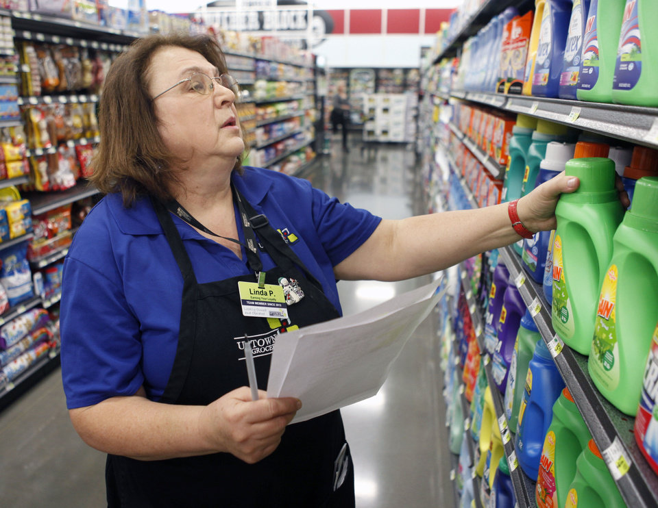 Photo - Buy For Less employee Linda Pelletier pulls shopping list items for a customer's Internet order at Uptown Grocery in Edmond, By Paul Hellstern, The Oklahoman  PAUL HELLSTERN
