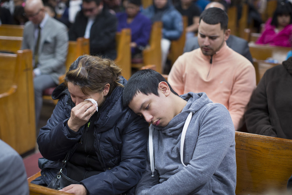 Photo - Parishioners mourn during Sunday services at the Church of God of Third Avenue as the congregation welcomed members of the Spanish Christian Church that was destroyed by Wednesday's explosion in the East Harlem neighborhood of New York, Sunday, March 16, 2014. The Spanish Christian Church had been located on the first floor of one of the destroyed buildings. On Saturday a crew at the blast site found a large Bible in the rubble and returned it to the church's pastor. (AP Photo/John Minchillo)