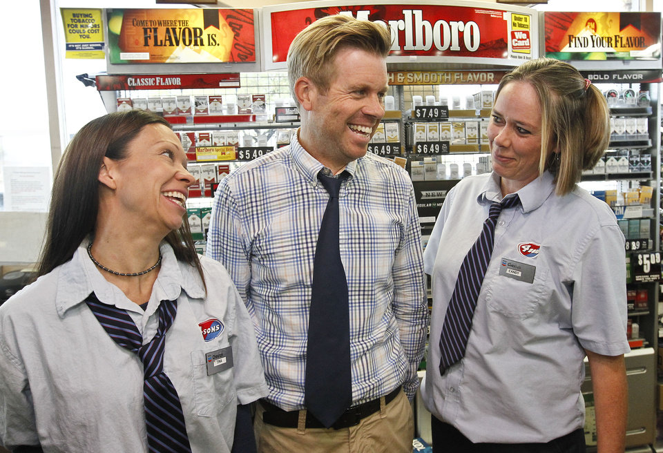 Photo - Store owner Eric Seitz, middle, laughs along with cashiers Tina Long, left, and Candy Browning at a 4 Sons Food Store where one of the winning tickets in the $579.9 million Powerball jackpot was purchased, Nov. 29, 2012, in Fountain Hills, Ariz.(AP Photo/Ross D. Franklin)