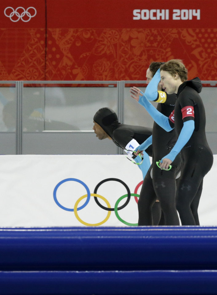 Photo - The U.S. speedskating team, Shani Davis, bending, Jonathan Kuck, background, and Brian Hansen catch their breath after competing in the men's speedskating team pursuit quarterfinals at the Adler Arena Skating Center during the 2014 Winter Olympics in Sochi, Russia, Friday, Feb. 21, 2014.  (AP Photo/Matt Dunham)