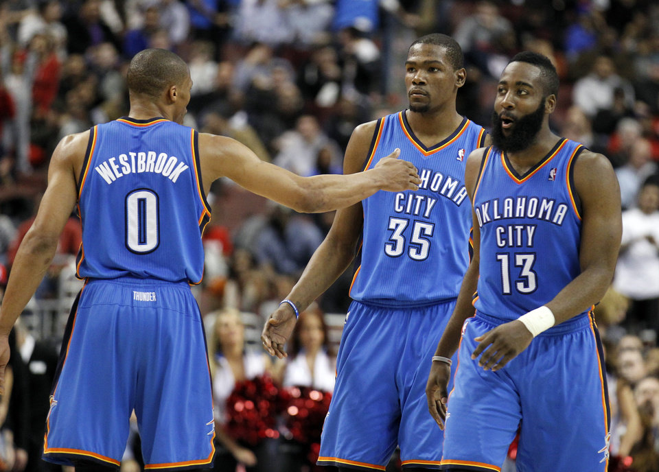 Photo - Oklahoma City Thunder's Russell Westbrook, left, reacts with teammates Kevin Durant (35) and James Harden (13) near the end of the first half of an NBA basketball game with the Philadelphia 76ers, Wednesday, Feb. 29, 2012, in Philadelphia. The Thunder won 92-88. (AP Photo/Alex Brandon) ORG XMIT: PXC116