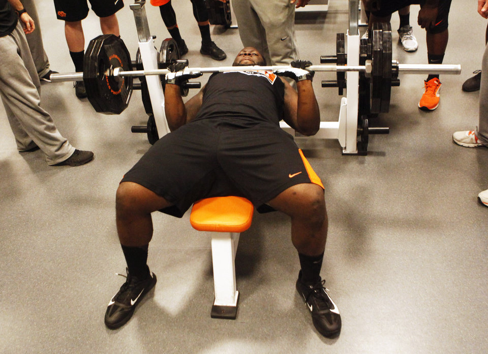 Photo - Defensive lineman Calvin Barnett lifts weights during a workout at Oklahoma State's pro day held at Boone Pickens Stadium in Stillwater on Thursday, March 13, 2014. Photo by KT King, The Oklahoman