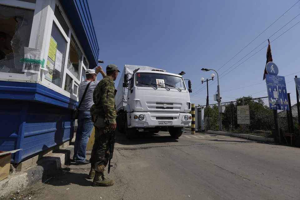 Photo - Ukrainian border guards look at the first aid truck as it passes the border post at Izvaryne, eastern Ukraine, Friday, Aug. 22, 2014. The first trucks in a Russian aid convoy crossed into eastern Ukraine on Friday, seemingly without Kiev's approval, after more than a week's delay amid suspicions the mission was being used as a cover for an invasion by Moscow. (AP Photo/Sergei Grits)