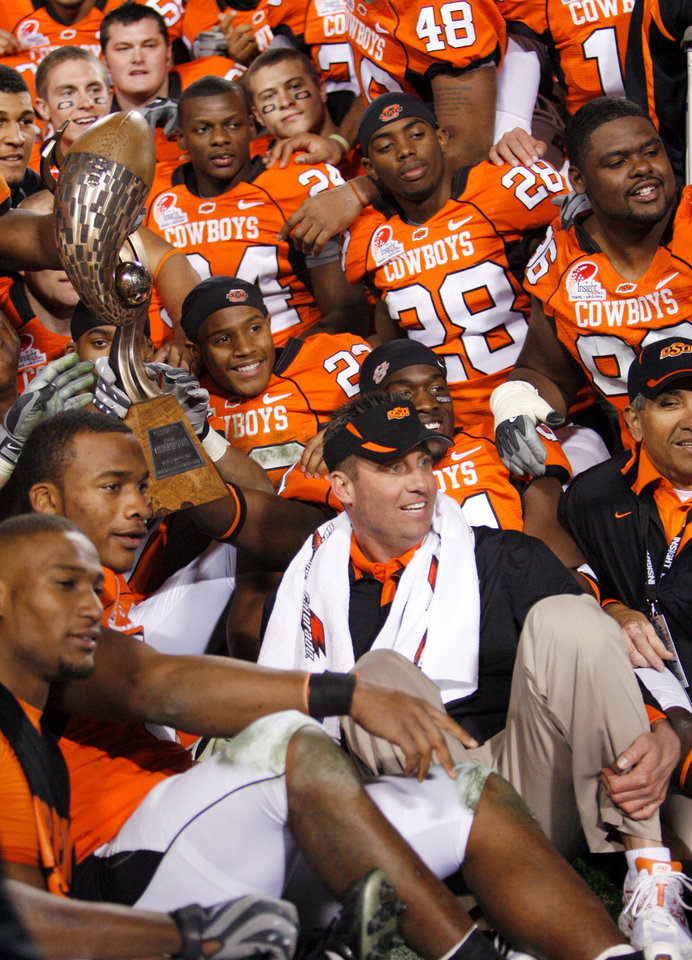 Photo - Head coach Mike Gundy and the OSU Cowboys pose for a photo with the Insight Bowl trophy after the Insight Bowl college football game between Oklahoma State University (OSU) and the Indiana University Hoosiers (IU) at Sun Devil Stadium on Monday, Dec. 31, 2007, in Tempe, Ariz. OSU won, 49-33. BY NATE BILLINGS, THE OKLAHOMAN