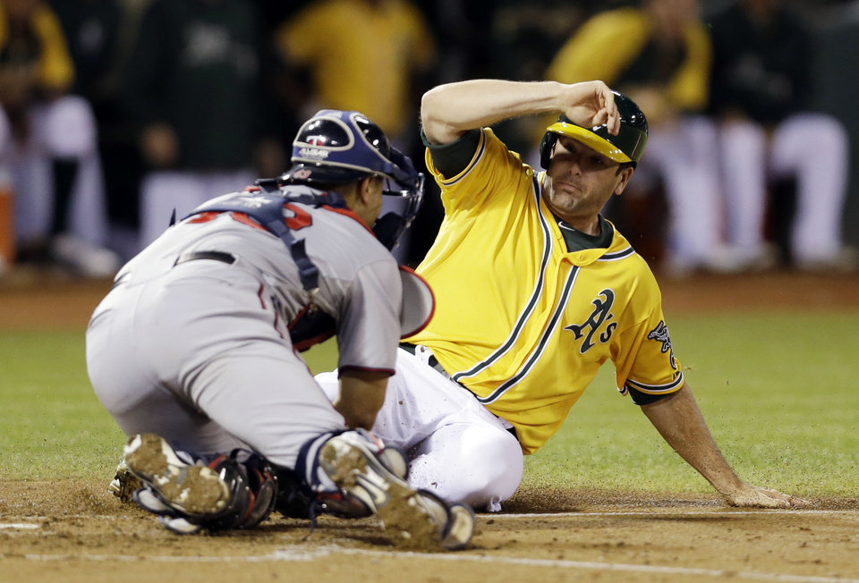 Oakland Athletics' Seth Smith, right, is tagged out at the plate by Minnesota Twins catcher Josmil Pinto during the second inning of a baseball game Thursday, Sept. 19, 2013, in Oakland, Calif. (AP Photo/Marcio Jose Sanchez)