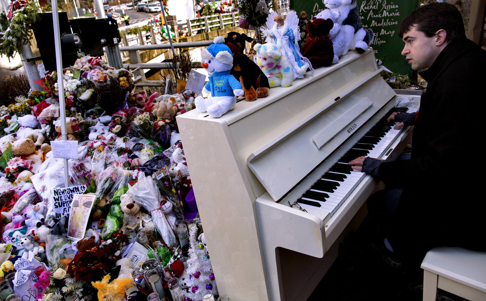 Among a memorial to the Sandy Hook Elementary students and teachers, Julian Revie of Ottawa, Canada, plays Christmas music on a piano he helped bring to the memorial, Tuesday, Dec. 25, 2012 in Newtown, Conn. People continue to visit memorials after gunman Adam Lanza walked into Sandy Hook Elementary School in Newtown, Conn., Dec. 14, and opened fire, killing 26, including 20 children, before killing himself. (AP Photo/Craig Ruttle)