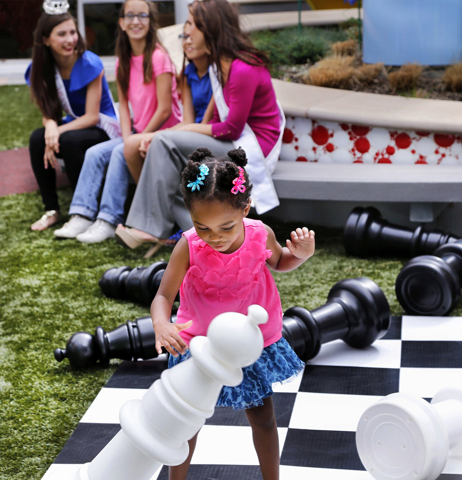 Photo -  Miracle Child Jalesa knocks over a chess piece while playing on the oversized chess board during the Marriane's Rentals for Special Events music video shoot for the upcoming Linen Fashion Show. In background are Miss NW Oklahoma Outstanding Teen Elizabeth Shelton, left, Miracle Child Martina and her sister Marley, and Miss Oklahoma 2013 Kelsey Griswold. Former patients team with Miss Oklahoma and other pageant queens to produce a video that will benefit Children's Miracle Network Hosptial, OU Children's Hospital. Photo by Jim Beckel, The Oklahoman   Jim Beckel -  THE OKLAHOMAN