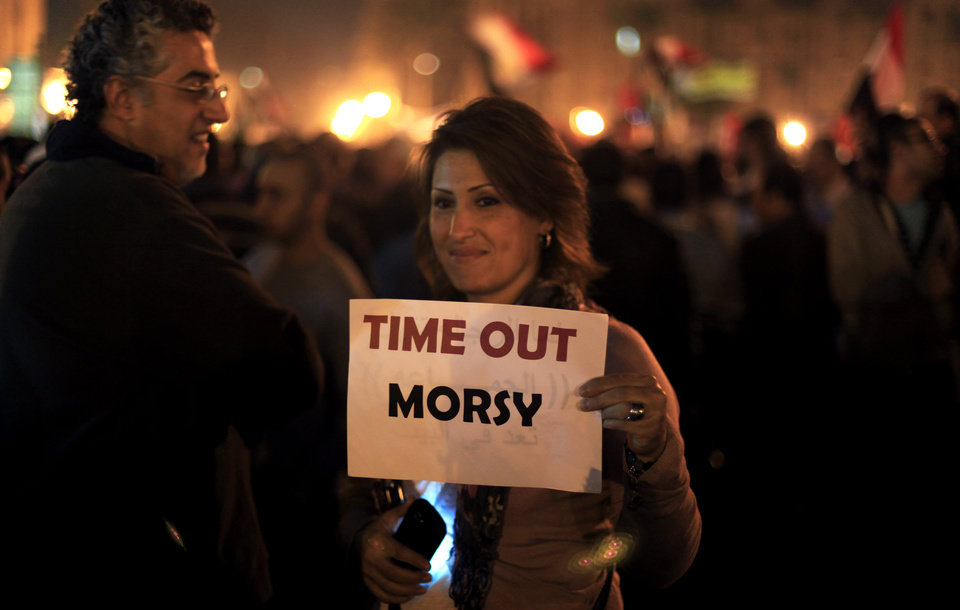 Photo -   A protester holds a placard against the Egyptian president at an opposition rally in Tahrir Square in Cairo, Egypt, Tuesday, Nov. 27, 2012. Thousands flocked to Cairo's central Tahrir square on Tuesday for a protest against Egypt's president in a significant test of whether the opposition can rally the street behind it in a confrontation aimed at forcing the Islamist leader to rescind decrees that granted him near absolute powers. (AP Photo/Khalil Hamra)