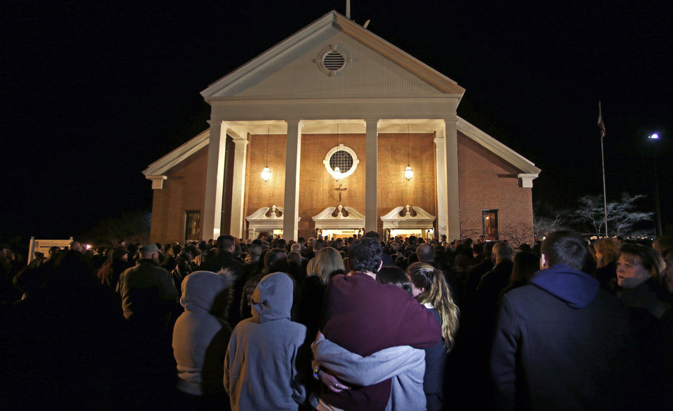 Photo - As hundreds stand outside St. Rose of Lima Roman Catholic Church, which was filled to capacity, a couple embrace during a healing service held in for victims of an elementary school shooting in Newtown, Conn., Friday, Dec. 14, 2012.  A gunman opened fire at Sandy Hook Elementary School in Newtown, killing 26 people, including 20 children. (AP Photo/Charles Krupa)