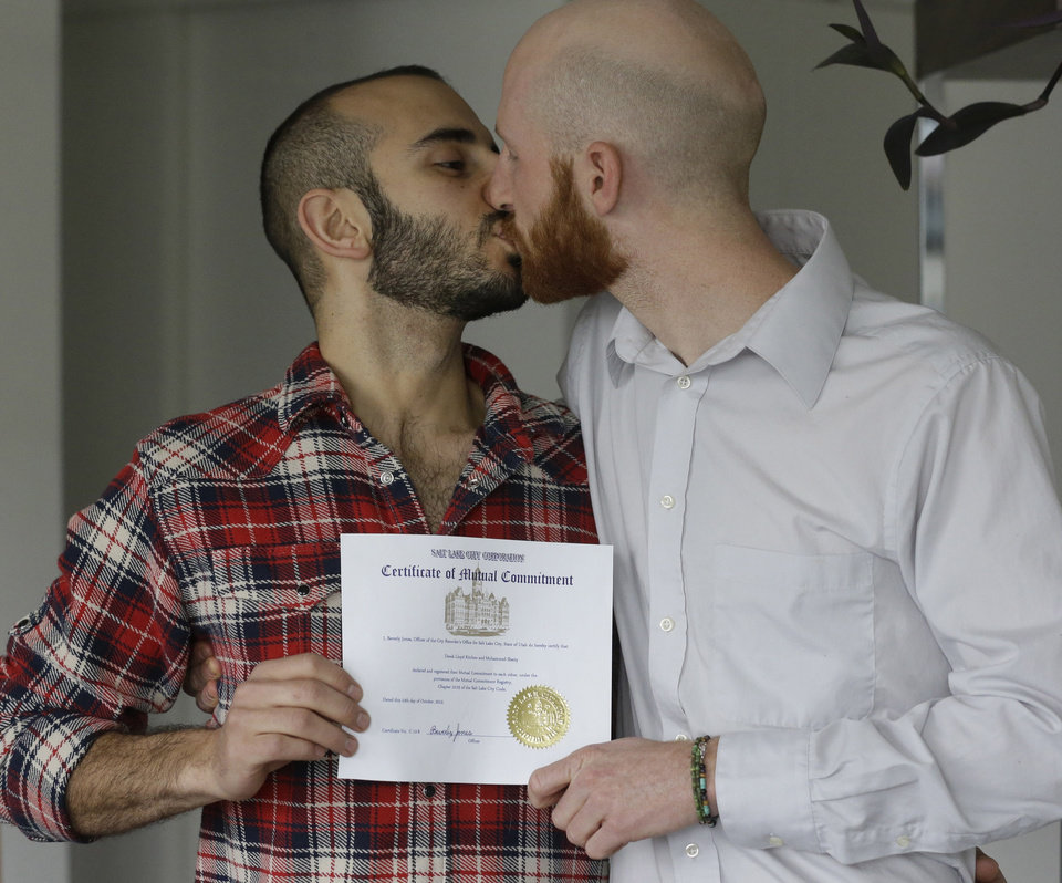 Photo - FILE - In this April 3, 2014, file photo, Derek Kitchen, right, and Moudi Sbeity kiss as they hold their certificate of mutual commitment at their home, in Salt Lake City. A federal appeals court on Wednesday ruled for the first time that states must allow gay couples to marry, finding the Constitution protects same-sex relationships and putting a remarkable legal winning streak across the country one step closer to the U.S. Supreme Court. (AP Photo/Rick Bowmer, File)