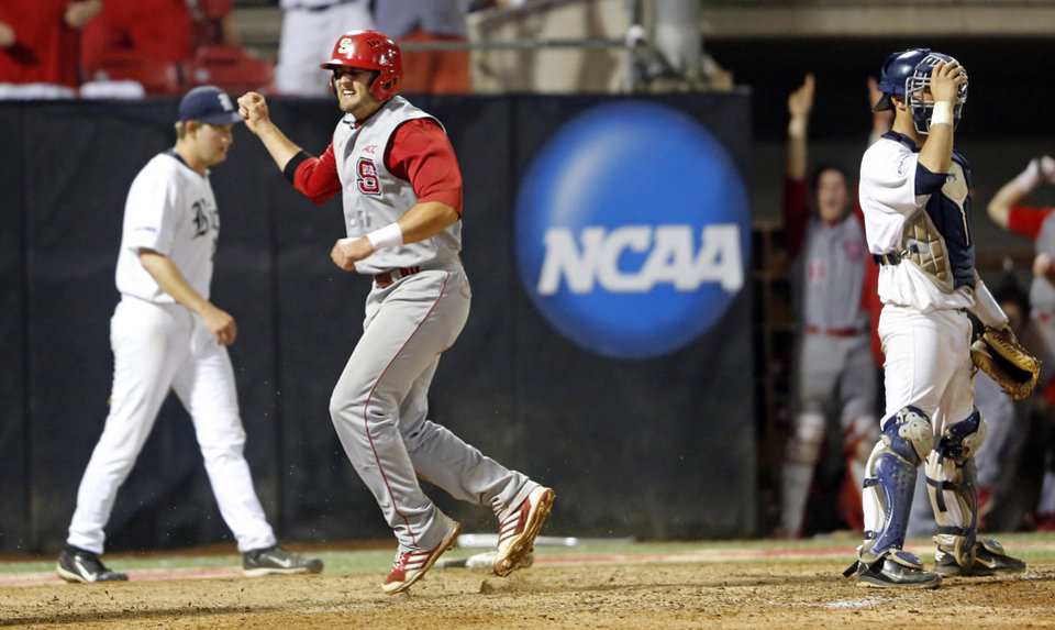 North Carolina State's Tarran Senay, center, celebrates scoring the go ahead run with Rice pitcher John Simms, left, and catcher Hunter Kopycinski, right, during the 17th inning of an NCAA college baseball tournament super regional game, Sunday, June 9, 2013, in Raleigh, N.C. State won 5-4 in 17 innings. (AP Photo/Karl B DeBlaker)