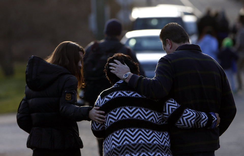 Photo - A woman is comforted after paying her respects at a memorial for shooting victims near Sandy Hook Elementary School, Saturday, Dec. 15, 2012 in Newtown, Conn.  A gunman walked into Sandy Hook Elementary School in Newtown Friday and opened fire, killing 26 people, including 20 children. (AP Photo/Jason DeCrow) ORG XMIT: CTJD120