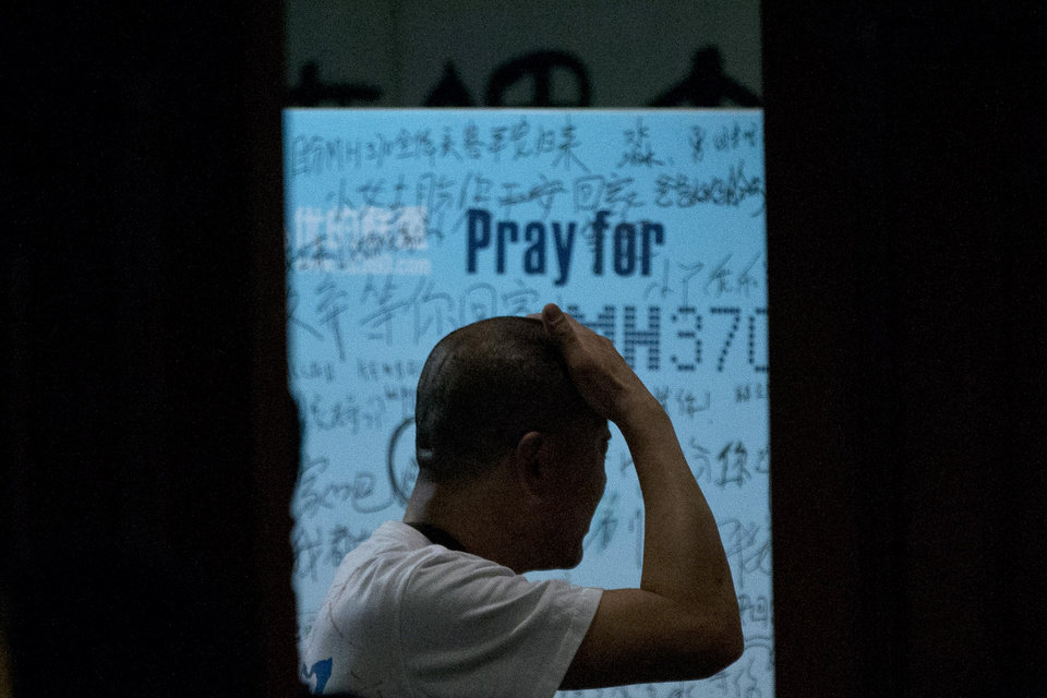 Photo - One of the relatives of Chinese passengers on board Malaysia Airlines Flight 370 rubs his head near a board covered with written wishes from relatives during a briefing given by Malaysian officials at a hotel in Beijing, China, Wednesday, March 26, 2014. Some of the wishes, partially seen, read,