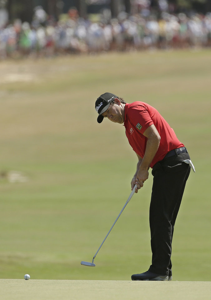 Photo - Erik Compton watches his putt on the first hole during the final round of the U.S. Open golf tournament in Pinehurst, N.C., Sunday, June 15, 2014. (AP Photo/Charlie Riedel)