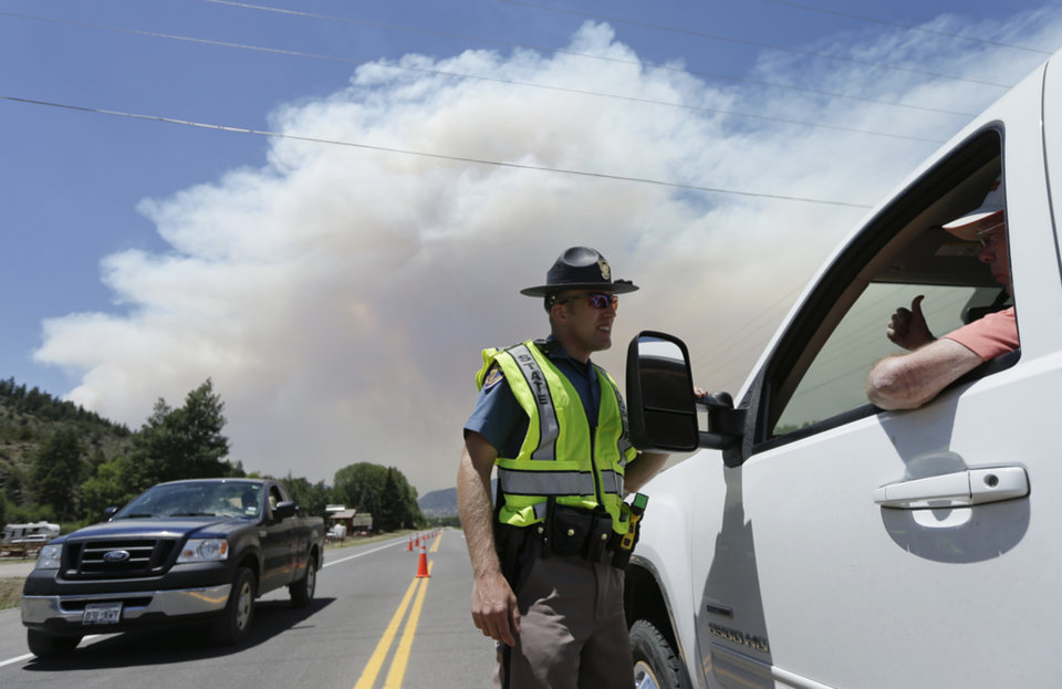 Photo - Colorado State Patrol officer Jessie Bartunek talks to a motorist as he stands at a checkpoint near South Fork, Colo., Sunday, June 23, 2013. A large wildfire near a popular summer retreat in southern Colorado continues to be driven by winds and fueled by dead trees in a drought-stricken area, authorities said Sunday. (AP Photo/Gregory Bull)