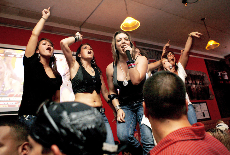 Photo - Coyote Ugly bartenders dance and sing on the bar during the opening of the bar Wednesday in Oklahoma City.PHOTO BY ASHLEY MCKEE, THE OKLAHOMAN