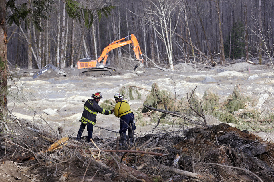 Photo - Bellevue, Wash., Fire Dept. Lt. Richard Burke, left, reaches across to shake hands with Benton County assistant fire chief Jack Coats as the two overlook the scene of a deadly mudslide Wednesday, April 2, 2014, in Oso, Wash. Officials have so far confirmed the deaths of 29 people, although only 22 have been officially identified in information released Wednesday morning by the Snohomish County medical examiner's office. (AP Photo/Elaine Thompson)