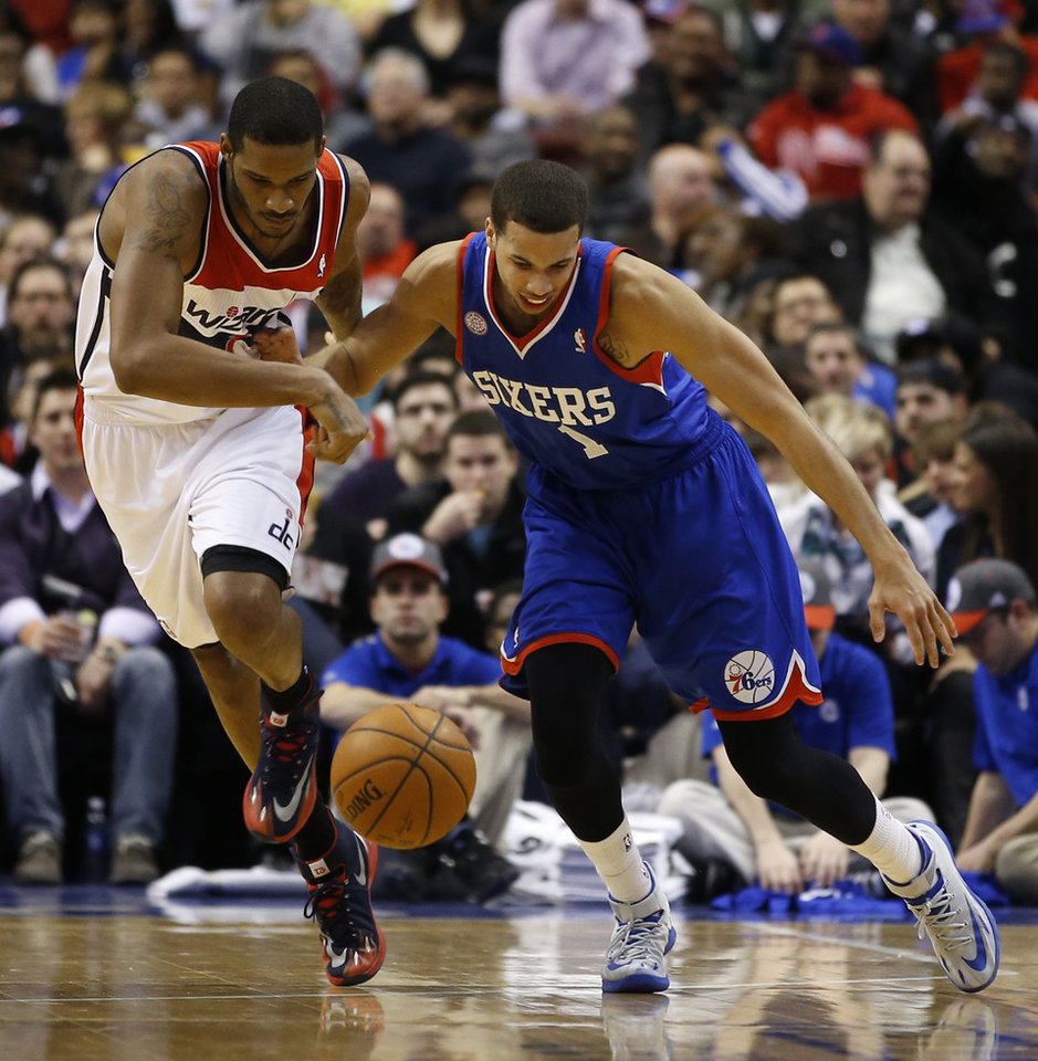 Photo - Philadelphia 76ers' Michael Carter-Williams, right, and Washington Wizards' Trevor Ariza battle for a loose ball during the first half of an NBA basketball game, Saturday, March 1, 2014, in Philadelphia. (AP Photo/Matt Slocum)