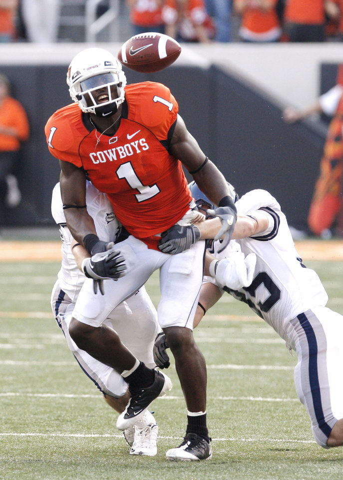 Photo - MATTHEW NORDSTROM: The ball pops out of Dez Bryant's hands after a catch as he is hit by Matt Nordstrom (50) left, and Travis Bradshaw (35) at the college football game between Oklahoma State University (OSU) and Rice University at Boone Pickens Stadium in Stillwater, Okla., Saturday, Sept. 19, 2009. Rice recovered. Photo by Doug Hoke, The Oklahoman. ORG XMIT: KOD