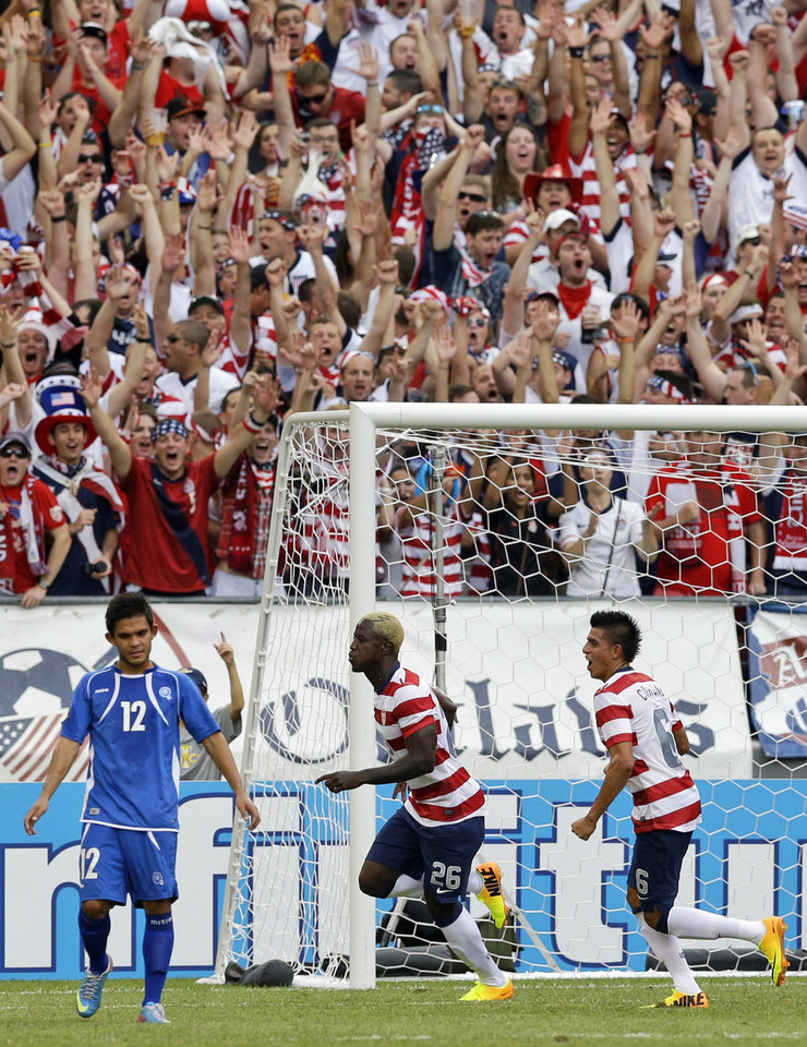 Photo - United States' Eddie Johnson, center, reacts between teammate Joe Corona and El Salvador's Andres Flores Mejia, left, after scoring a goal during the second half in the quarterfinals of the CONCACAF Gold Cup soccer tournament, Sunday, July 21, 2013, in Baltimore. The United States won 5-1. (AP Photo/Patrick Semansky)