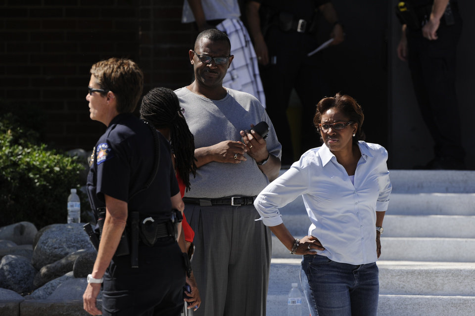 Photo - State Representative Rhonda Fields, left, arrives at Gateway High School in Aurora, Colo, where witnesses are being interviewed by authorities Friday, July 20, 2012. AA gunman wearing a gas mask set off an unknown gas and fired into the crowded movie theater killing 12 people and injuring at least 50 others, authorities said.  The suspect is identified as 24-year-old James Holmes. (AP Photo/The Denver Post, Craig F. Walker) TV, INTERNET AND MAGAZINES CALL FOR RATES AND TERMS ORG XMIT: CODEN235