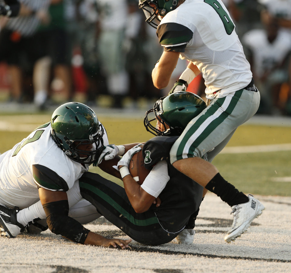 Photo - Edmond Santa Fe's Jeremy Cox and Kaden Mendenhall bring down Norman North's Cale Horton during a high school football scrimmage at Harve Collins Field in Norman, Okla., on Thursday, Aug. 21, 2014. Photo by Steve Sisney, The Oklahoman