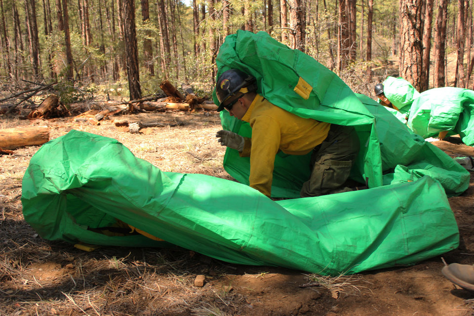 Photo - ADDS IDENTIFICATION - In this April 12, 2012 photo provided by the Cronkite News, Granite Mountain Hotshots crew member Shane Arollado trains with others on setting up emergency fire shelters outside of Prescott, Ariz. On Sunday, June 30, 2013, 19 members of the Prescott-based crew were killed in the deadliest wildfire involving firefighters in the U.S. for at least 30 years. The firefighters were forced to deploy their emergency fire shelters - tent-like structures meant to shield firefighters from flames and heat - when they were caught near the central Arizona town of Yarnell, according to a state forestry spokesman. (AP Photo/Cronkite News, Connor Radnovich)