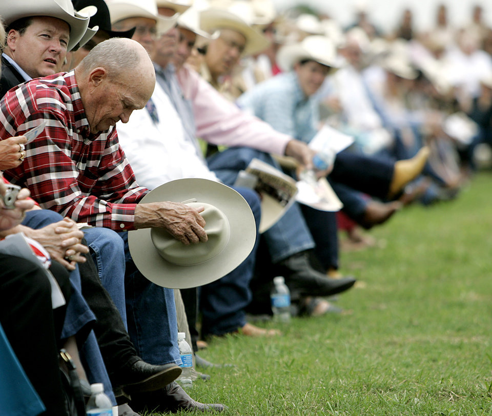 Photo - Howard Harris, a long time friend of Jim Shoulders, bows his head during funeral services for Jim Shoulders in Henryetta, Okla., on Sunday,  June 24, 2007. By John Clanton, The Oklahoman