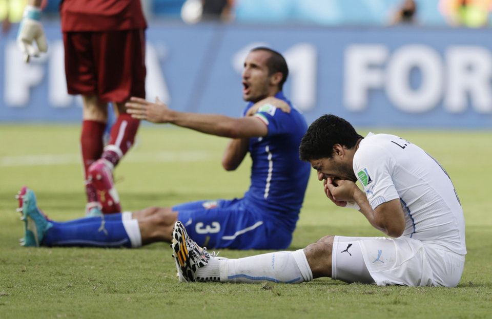 Photo - Italy's Giorgio Chiellini complains after Uruguay's Luis Suarez ran into his shoulder with his teeth during the group D World Cup soccer match between Italy and Uruguay at the Arena das Dunas in Natal, Brazil, Tuesday, June 24, 2014. (AP Photo/Ricardo Mazalan)