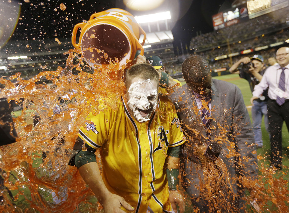 Photo - Oakland Athletics' Stephen Vogt gets a Gatorade shower after making the game-winning hit to beat the Detroit Tigers 1-0 in Game 2 of the American League baseball Division Series in Oakland, Calif., Saturday, Oct. 5, 2013. (AP Photo/Marcio Jose Sanchez)